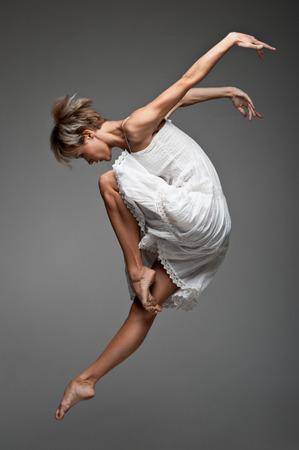 giovane e bella femmina caucasica ballerina saltando su sfondo grigio Archivio Fotografico