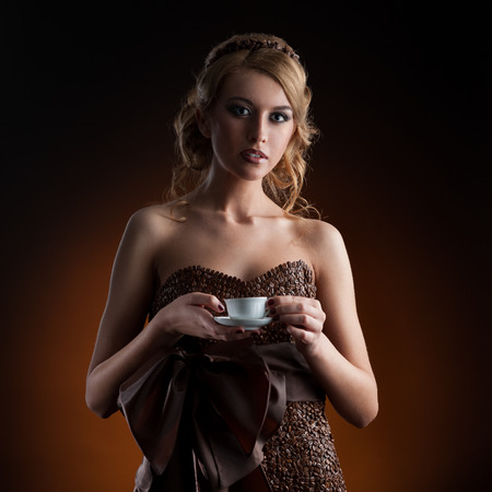 young sensual caucasian woman in dress made of coffee beans standing over gradient orange background photo