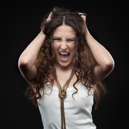 brown hair: screaming casual brunette woman over black background Stock Photo