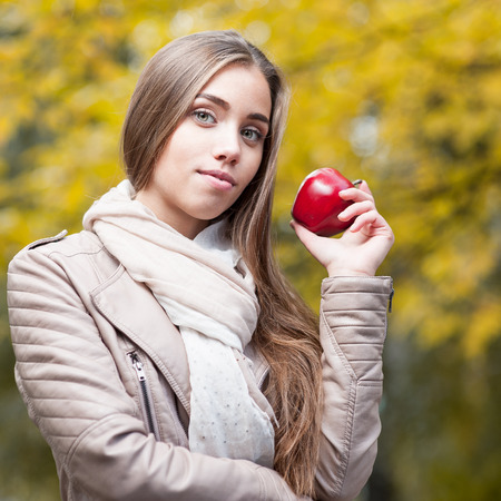 young happy casual caucasian woman in autumn park smiling while holding red apple photo