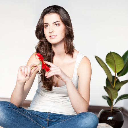 beautiful young thoughtful casual brunette woman sitting on wool plaid and holding red flower photo