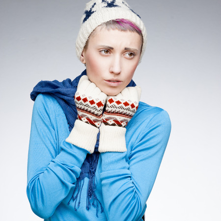 studio portrait of young attractive caucasian girl in winter clothing with sick expression photo