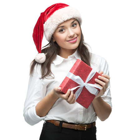 young cheerful caucasian brunette businesswoman in santa hat holding gift  isolated on white photo