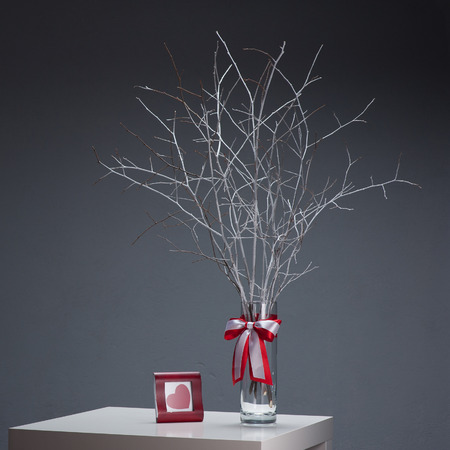 white tree in glass vase and res photo frame on white table over gray background photo