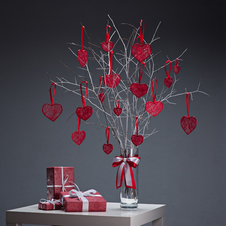 tree with red hearts in glass vase and red gifts on white table over gray background photo