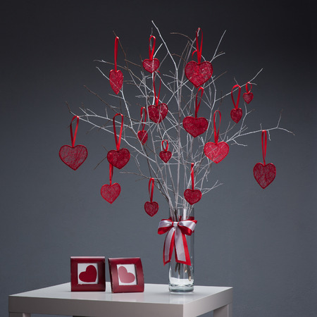 tree with red hearts in glass vase and photo frame on white table over gray background photo