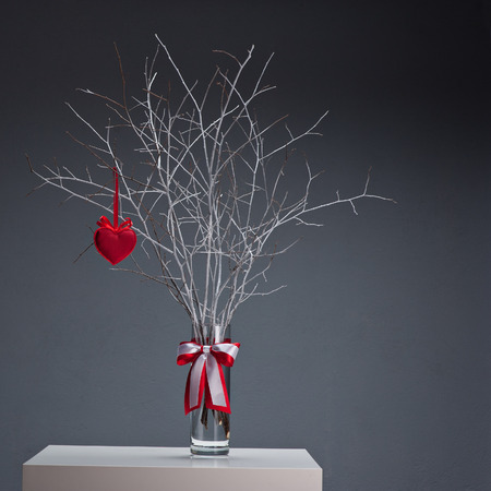 tree with red heart in glass vase on white table over gray background photo