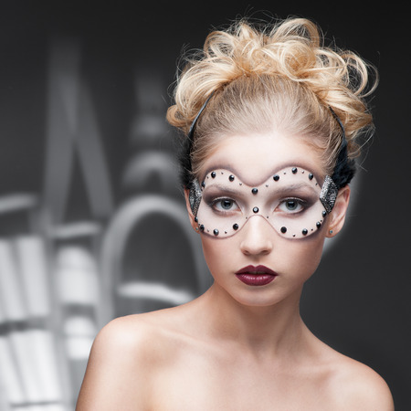beauty portrait of young caucasian blond woman in fantasy make-up over cartoon style houses on background photo