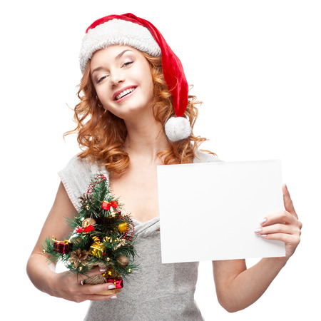 studio portrait of young cheerful red-haired caucasian girl in santa hat which holding sign on white photo