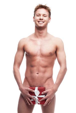 naked man: hombre joven desnudo que sostiene rojo pequeño regalo y sexy mirando a cámara aislada en blanco