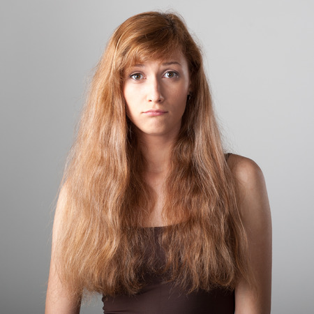 resentful: resentful casual caucasian girl with long brown hair on gray background