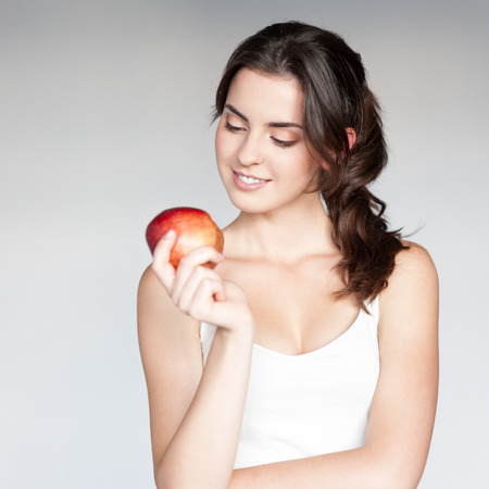 white singlet: beautiful caucasian thoughtful young woman  in white singlet holding red apple over gray background Stock Photo