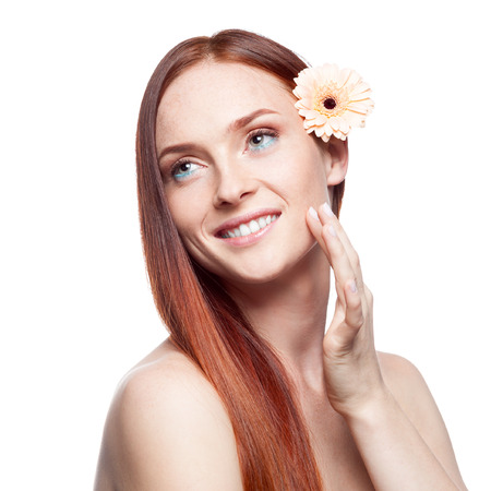 portrait of young smiling caucasian red haired woman with flower in hair isolated on white photo