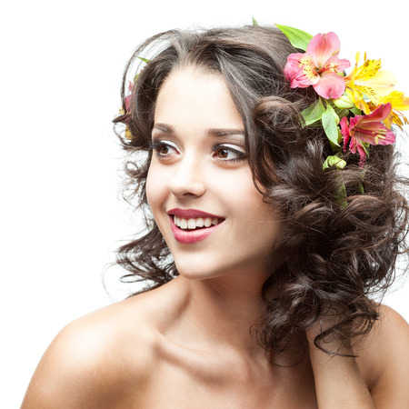 caucasian young smiling woman with pink lily flower in hair isolated on white photo