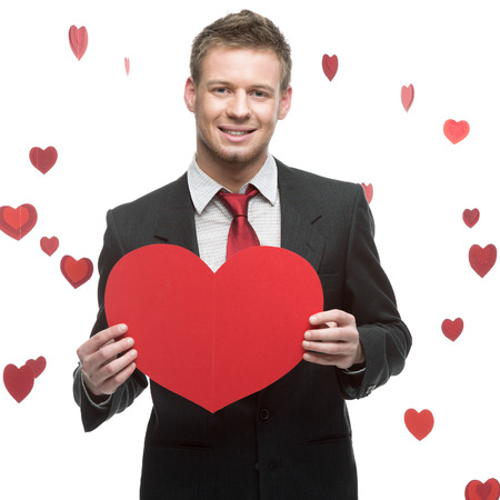 caucasian young businessman in gray suit holding sign in form of big red heart with sexy look photo