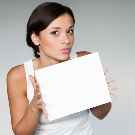 white singlet: cheerful young woman in white singlet holding sign over gray background