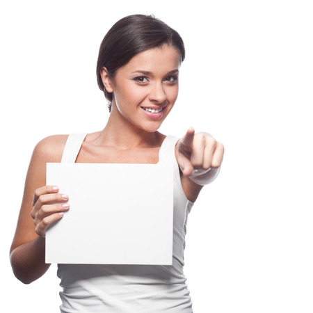 white singlet: casual brunette young woman in white singlet holding sign and pointing at camera isolated on white