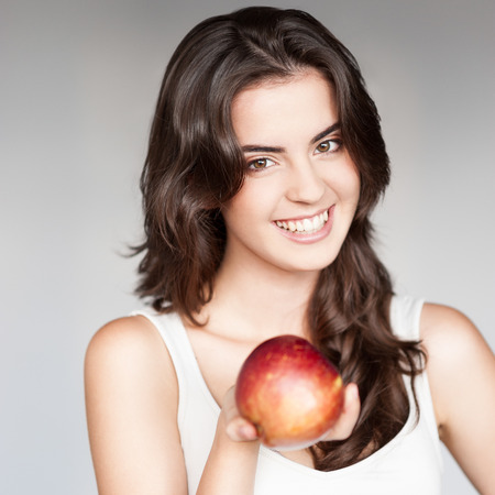 white singlet: young casual caucasian brunette  woman in white singlet holding red apple over gray background Stock Photo