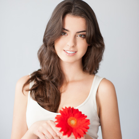 white singlet: beautiful smiling caucasian brunette woman in white singlet holding red flower over gray background