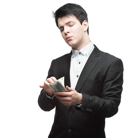caucasian thoughtful young businessman in black suit counting money isolated on white photo