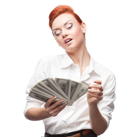 young caucasian red-haired admiring business woman counting money isolated on white photo