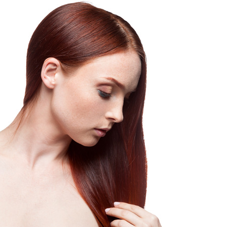 young caucasian red haired woman touching her hair isolated on white photo
