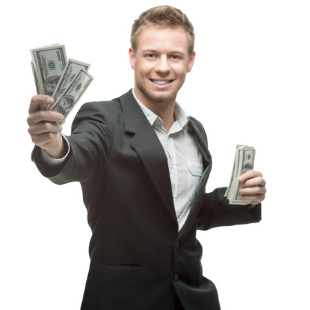 cheerful caucasian young businessman in gray suit holding money isolated on white background 免版税图像