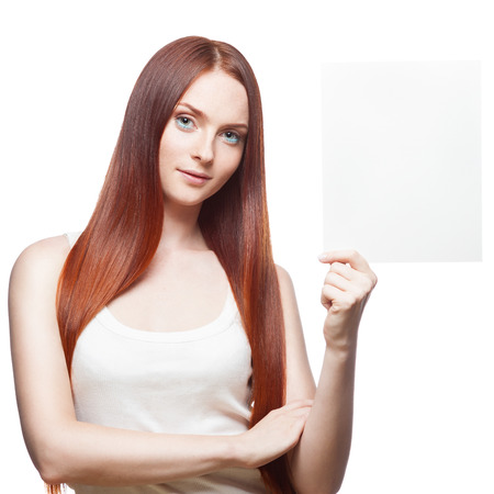 smirking: attractive young  casual caucasian red haired smirking girl holding sign isolated on white Stock Photo