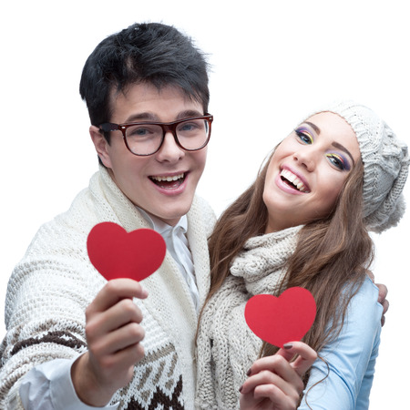 young casual caucasian brunette couple in winter clothing holding red hearts and looking at camera with happy smile photo