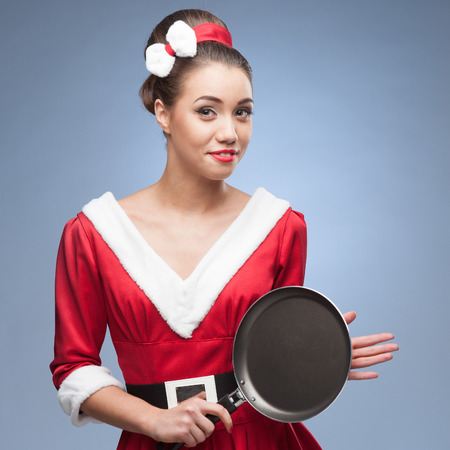 young cheerful retro girl in red vintage dress holding frying pan photo