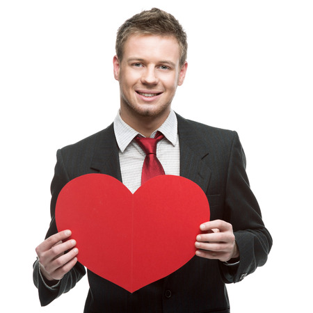 caucasian young businessman in gray suit holding sign in form of big red heart . isolated on white photo