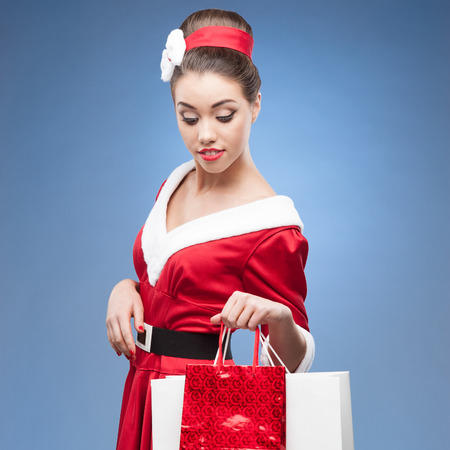 young cheerful retro girl in red vintage dress holding shopping bags photo