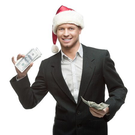 young smiling caucasian businessman in black suit and santa hat holding money isoalted on white photo