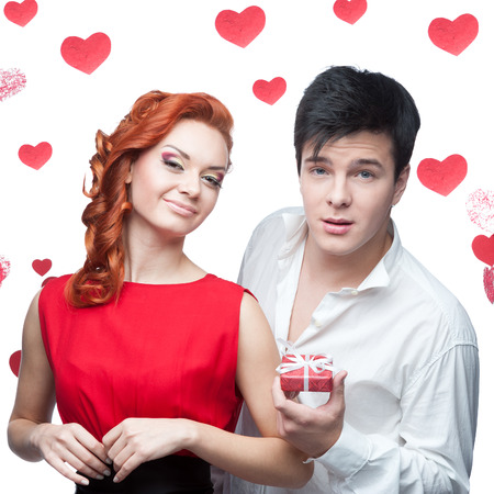 young smiling man and woman in red dress holding small red gift photo