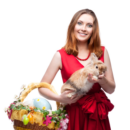 cheerful young woman in red dress holding easter basket and rabbit isolated on white photo