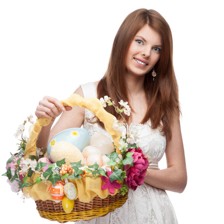 cheerful red-haired woman in short white dress holding easter basket isolated on white photo