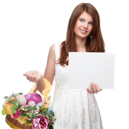 cheerful red-haired woman in short white dress holding easter basket and sign isolated on white photo