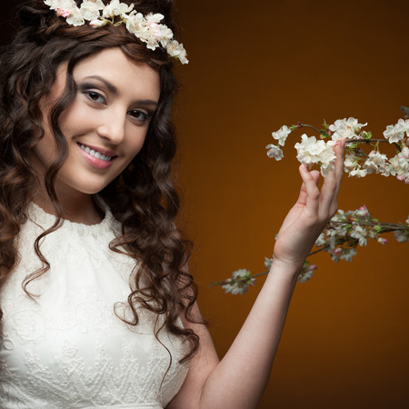 young smiling brunette woman in long white dress and flowers in hair standing near flowering tree over orange background photo