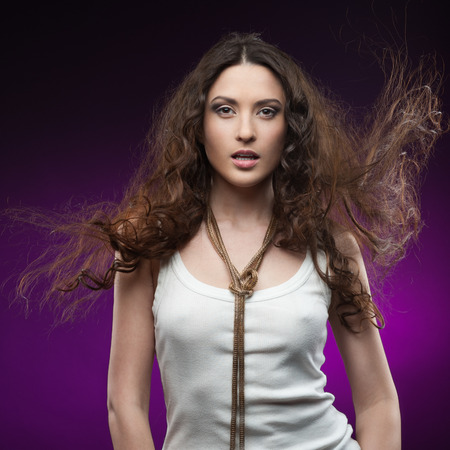 young casual sexy brunette woman standing over purple background photo