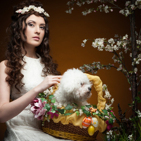 young sensual brunette woman in long white dress and flowers in hair holding basket with puppy  over orange background photo
