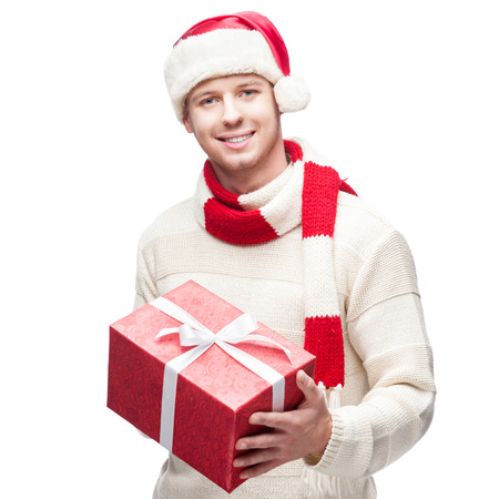young casual caucasian man in santa hat holding red christmas gift isolated on white background photo