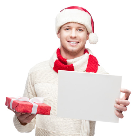 young casual caucasian man in santa hat holding red christmas gift and sign isolated on white background photo