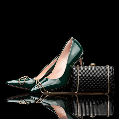 high heel shoes: composition of green female high heel shoes and black clutch isolated on black