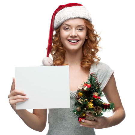 cheerful red-haired caucasian girl in santa hat  holding sign on white photo