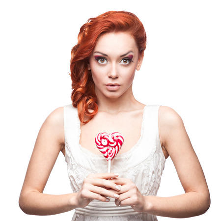 cheerful caucasian red-haired surprised young woman holding lollipop. isolated on white photo