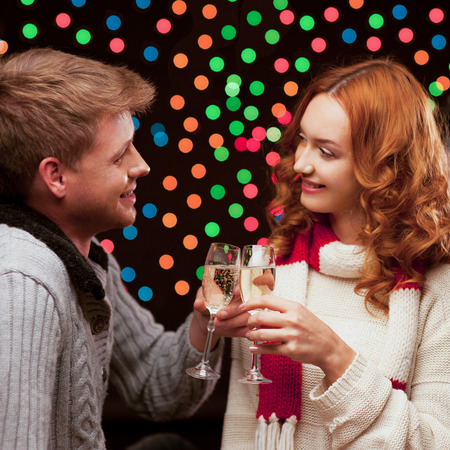 young happy smiling casual couple with wineglasses over christmas tree and lights on background. shallow depth of field. soft focus. warm light photo