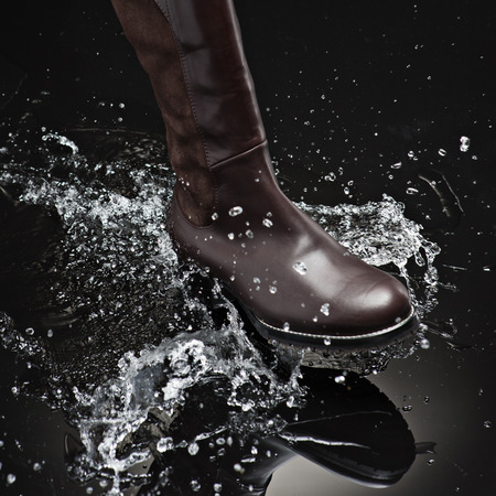brown leather female boot splashing water