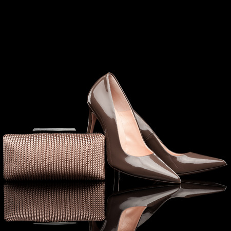 high heel shoes: composition of brown female high heel shoes and clutch isolated on black