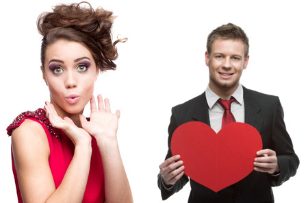 young surprised woman and handsome man holding red heart isolated on white background photo