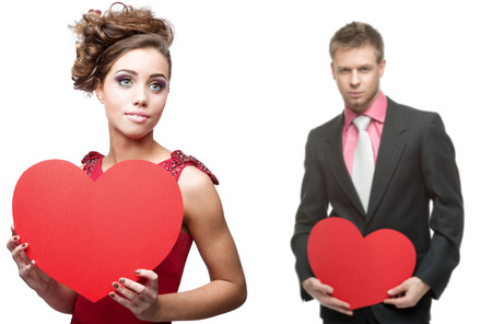 young sensual woman and handsome man holding red heart isolated on white background photo